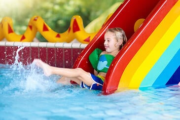 bigstock-Child-On-Swimming-Pool-Slide--235586884